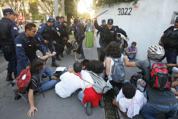 Police officers attack student demonstrators with their truncheons. Photo by Alejandro Velazco.