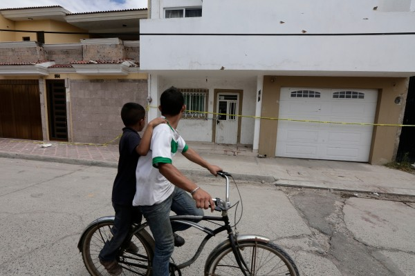 Two boys pass a bullet-ridden home in Ocotlán. (Photo by Victor Hugo Ornelas)