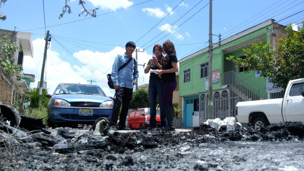 Locals look down at the burnt-out remains of their car. Photo by Victor Hugo Ornelas.