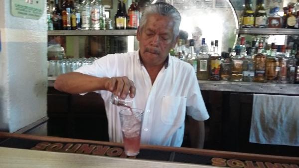 "Cuco the waiter prepares the house cocktail ""Nalgas Alegres"" (Happy Buttocks)."